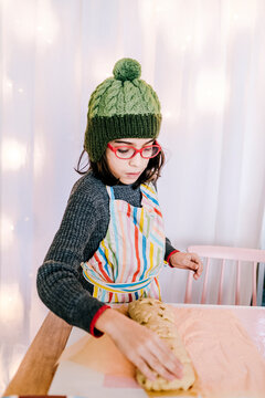 Child wearing glasses decorating bread dough by pink chair