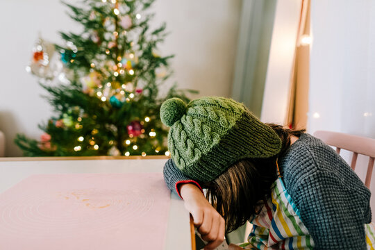 Child wearing green pom hat reading book by pink table and christmas tree