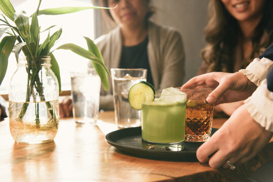 Low profile focus on specialty cocktails being passed by server