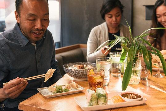 Three friends sitting to eat food at Vietnamese restaurant