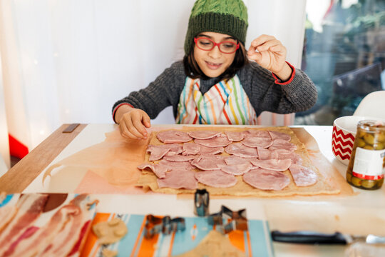 Child  wearing green hat and red glasses making ham and bacon holidays bread