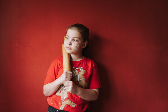Girl standing and holding a wooden rolling pin as a baseball bat