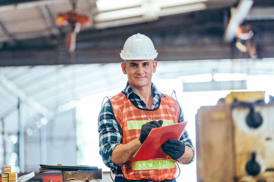Portrait of engineer foreman in hardhat working on construction repair checklist document clipboard in industrial manufacturing factory. worker man in protective uniform work hard. copy space