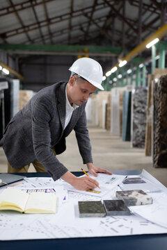 Modern worker of marble organization drawing blueprint