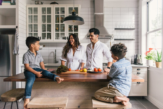 Mom and dad laughing at kids while making lunch in renovated kitchen