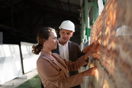 Architect with warehouse manager exploring stone slab