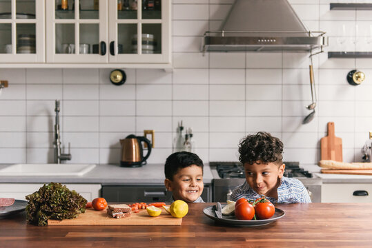 Young boys peek over kitchen counter to look at lunch with silly faces