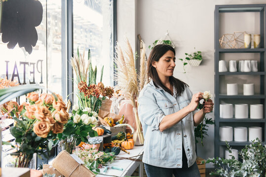 Adult woman florist carefully styling a single rose in flower shop