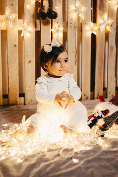 a baby girl in a photo set taking christmas photos