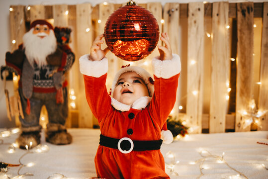 A baby girl disguised as Santa Claus trying to catch a Christmas ball