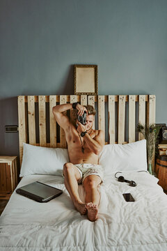 a man takes a picture while working with his mobile phone and laptop in a hotel bed.