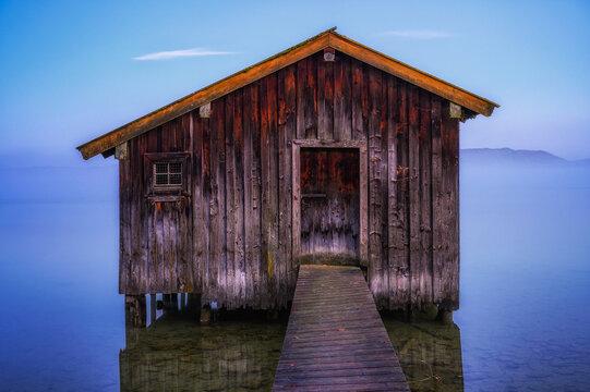 Einsames Bootshaus am frühen Morgen im Nebel über dem Kochelsee.