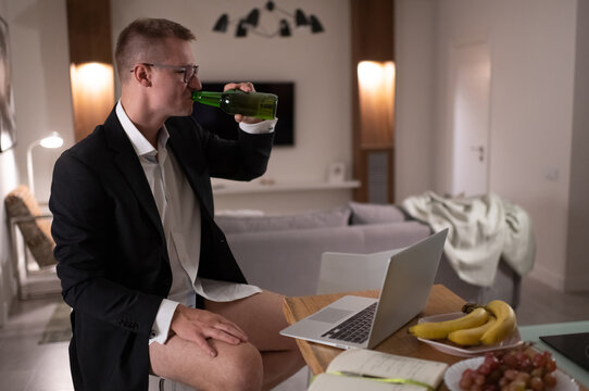 Man drinking beer during work at home