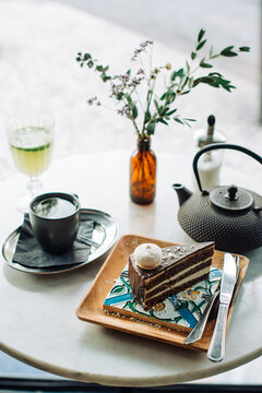 Slice of chocolate cake, teapot, cup of tea on table in outdoors cafe