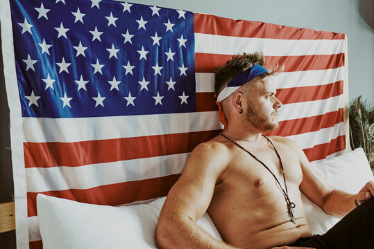 A young man in bed with the American flag behind him