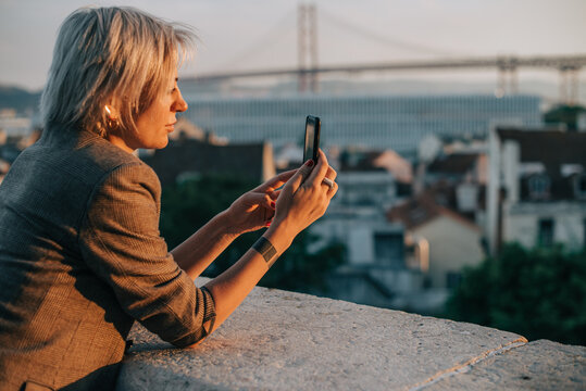 Blond woman in jacket taking cityscape photos with her smartphone