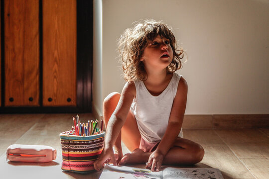 Curly haired little girl sitting on wooden floor and coloring book