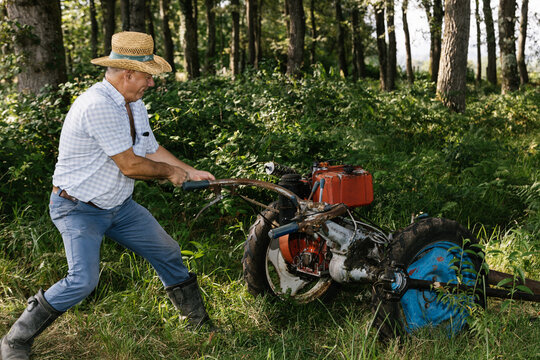 Old farmer repairing a mower on sunny day. agriculture concept