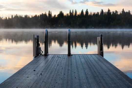 Swimming dock with ladder near calm lake at sunset with reflection