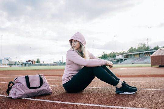 woman sat on a running track with a sports bag waiting