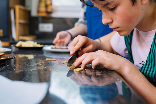 Young teen cutting cookies with knife on countertop at kitchen
