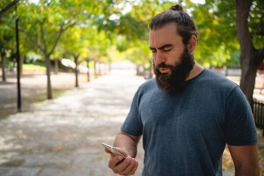 Man on a park checks his training results on his smartphone