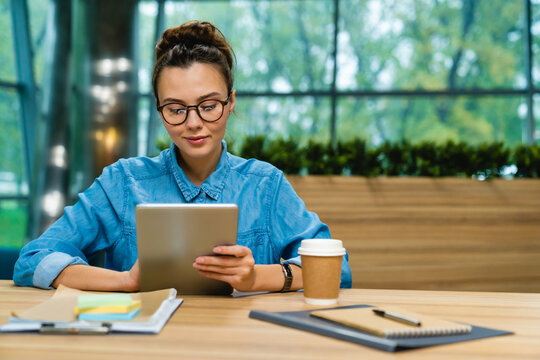 Nice-looking young caucasian businesswoman using tablet at the desk in modern office
