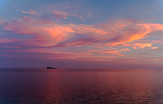 Sunset in Benidorm / Valencia / Spain with a cloudy blue and orange sky and an island at the horizon of the Mediterranean Sea with a orange, red , blue and pink color. Horizontal photo