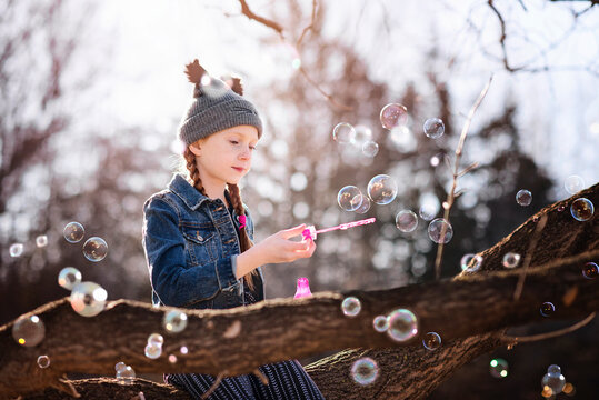 Young Girl Blowing Bubbles Outdoors in Fall