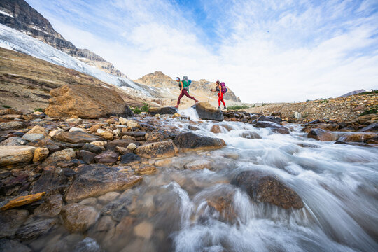 Female Backpackers Crossing River While Hiking Beautiful Iceline Trail