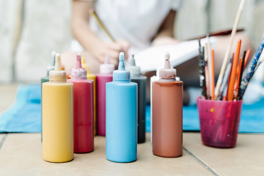 color painting bottles in front of a white girl painting with a brush her picture sitting on a terrace. Horizontal photo
