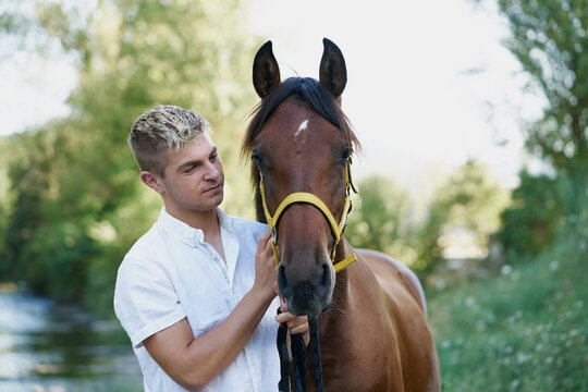 Portrait of a blond young man with a horse
