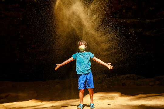 A boy wearing face mask stands in a sunlit gorge tossing up gold sand