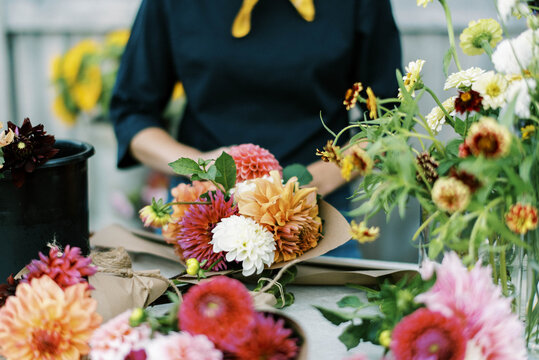 Female business owner and flower farmer arranging dahlia bouquets