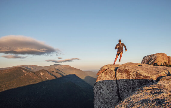 man runs along edge of cliff on top of mountain at sunset in Maine