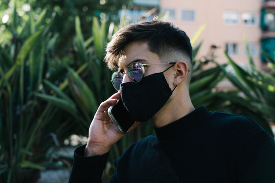 boy with sunglasses and mask calls on the phone