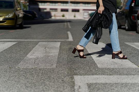 Woman walking on a zebra crossing wearing high heels holding a jacket