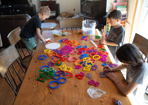 Kids playing with cookie cutters at a table for homeschool