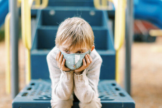 A boy looking sad at a playground with his face mask on