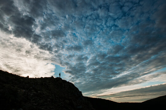 person on mountain in silhouette with dramatic clouds in Maine