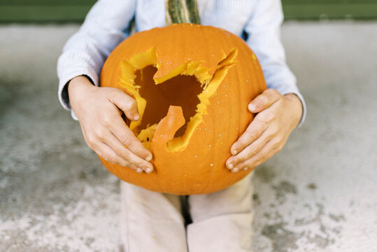 Little boy sitting on his porch showing off carved halloween pumpkin