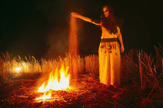 Woman in halloween witch costume throws the ashes of the dead.