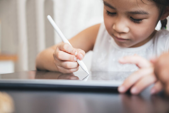 Little girl with tablet and stylus learning drawing online