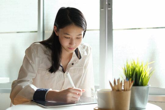 Young student girl using degital pen write on tablet.