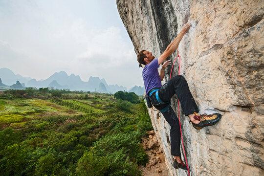 "man climbing on the limestone cliff ""White Mountain"" in Yangshuo"