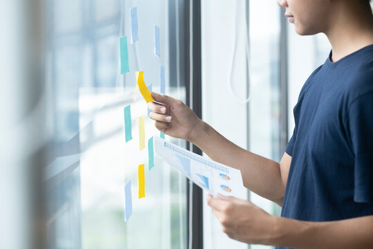 Creative man reading sticky notes on glass wall