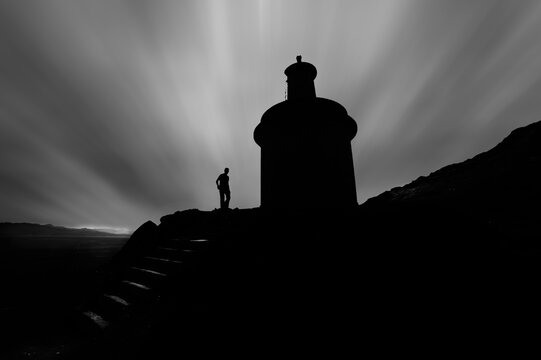 silhouette of lighthouse and man under a sea of clouds
