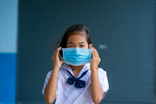 Asian children in school uniform wearing protective mask to Prot