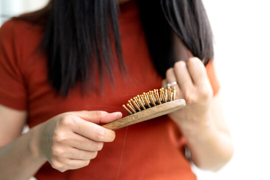 long loss hair fall on woman brush with and woman looking at her