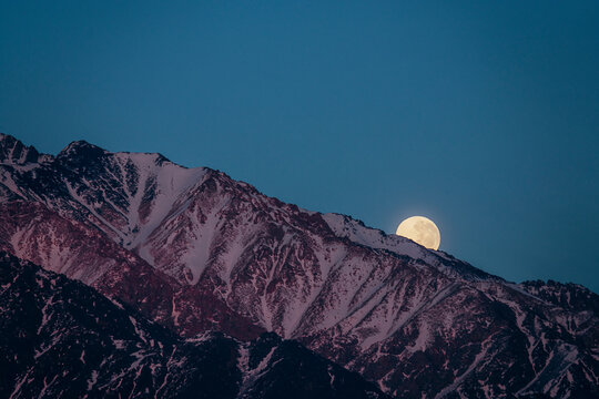full moon hiding behind the andes mountain range in mendoza argentina